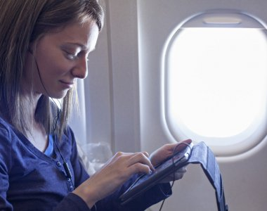 Plane Passenger In Airplane Using Tablet