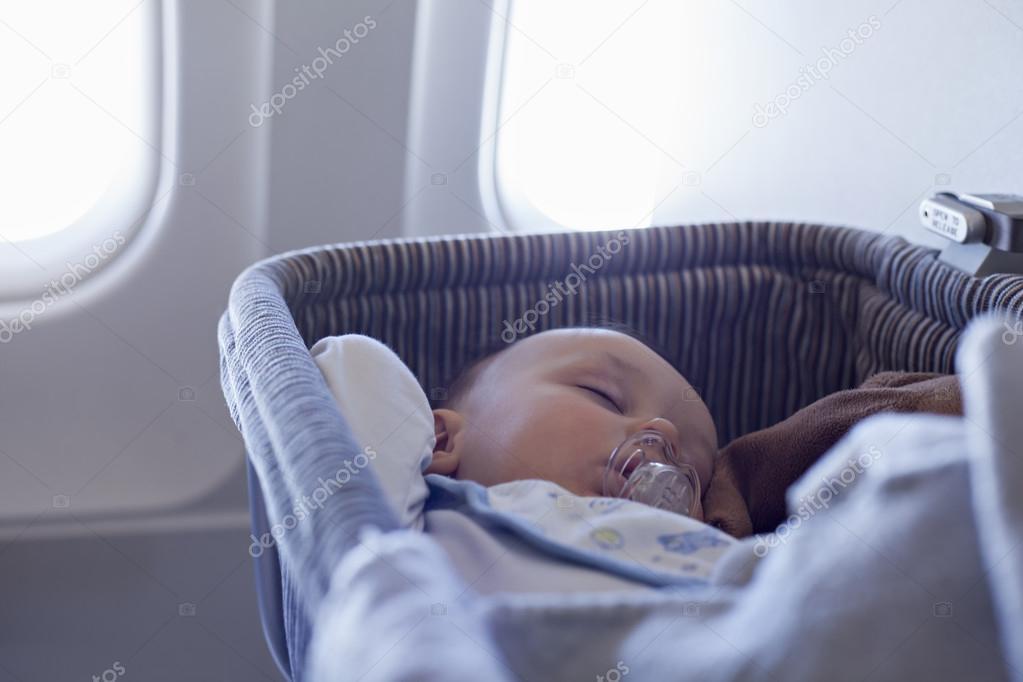 Jungen schlafen im stubenwagen im flugzeug u stockfoto dangubic