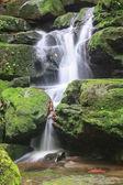 cascata e rocce ricoprono di muschio