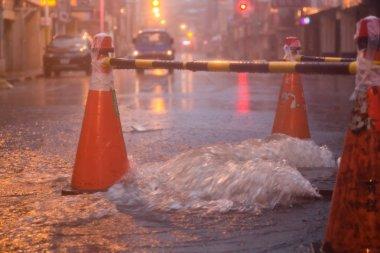 Orange cones around overflowing manhole