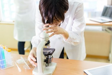 Asian female scientist looking into microscope