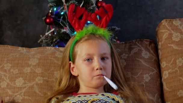 Szomorú, beteg gyerek lázmérővel a szájában szilveszterkor. Aranyos kislány ünnepi vörös szarvas szarvakkal sír könnyes szemekkel. Depressziós vírus betegség beteg ideges boldogtalan gyerek ünnepli a karácsonyt