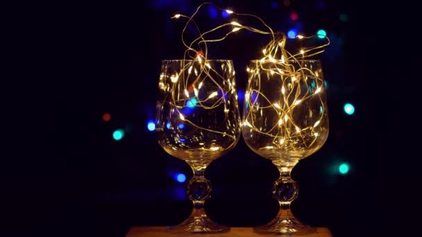 Křišťálové sklenice na víno zdobené zlatě zářícím věncem na vánočním stolku bokeh světla na pozadí. Romantická novoroční večeře se šampaňským pro zamilované páry. Kouzelné zimní prázdniny atmosféra