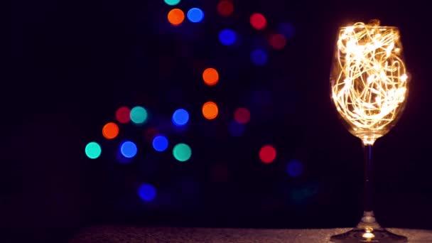 Kristály pezsgő üveg díszített arany ragyogó koszorú a karácsonyi asztalra bokeh fények háttér. Romantikus szilveszteri vacsora szerelmes fehér borpárral. Varázslatos téli ünnepek hangulata