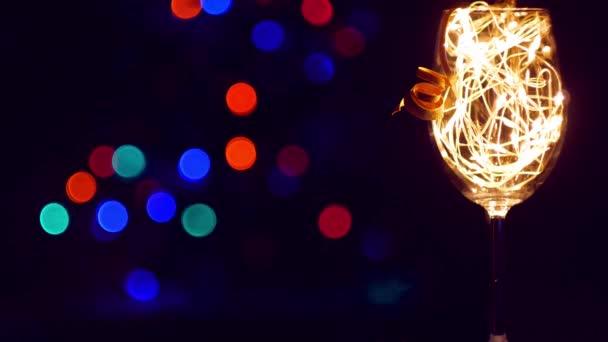 Kristall-Champagner-Glas mit goldenen leuchtenden Girlanden auf dem Weihnachtstisch Bokeh Lichter Hintergrund dekoriert. Romantisches Silvesterdinner mit einem verliebten Weißweinpaar. Magische Winterurlaubsatmosphäre