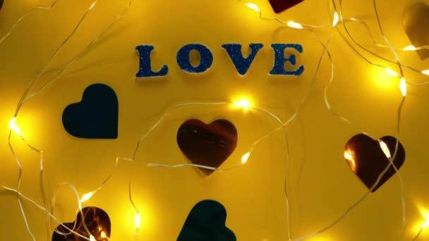 Valentýn Láska třpyt nápis text na pastelově žluté pozadí srdce konfety, kreativní ploché minimální koncept. 4K blahopřání top view sociální média prodej banner design. Jasné barvy vebrantu.