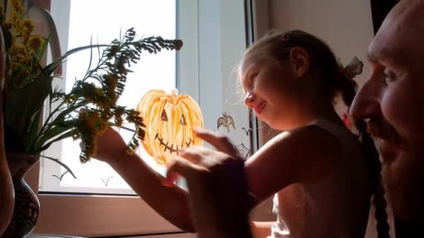Child with father painting pumpkin on window preparing to Halloween Little girl with dad drawing decorating room paper bats celebration autumn holiday home.Creative family leisure lockdown new reality