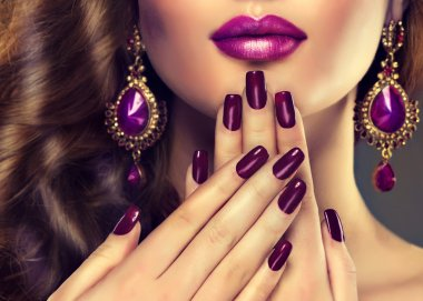 female face with purple manicure