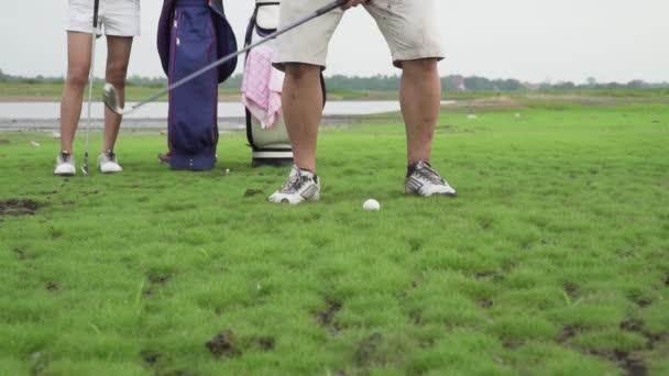 Záběry B Roll of couple lover in action of playing golf together. Golfový míček daleko od drsné na fairway, Těžké časy zůstat spolu v rodinném hřišti. Zkouška golfu na poli přírody.