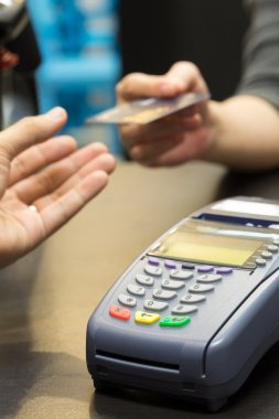 Credit Card Machine on the Table with Woman handing over credit