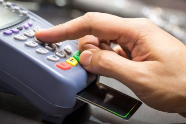 Close Up Of Hand With Credit Card Swipe Through Terminal For Sal