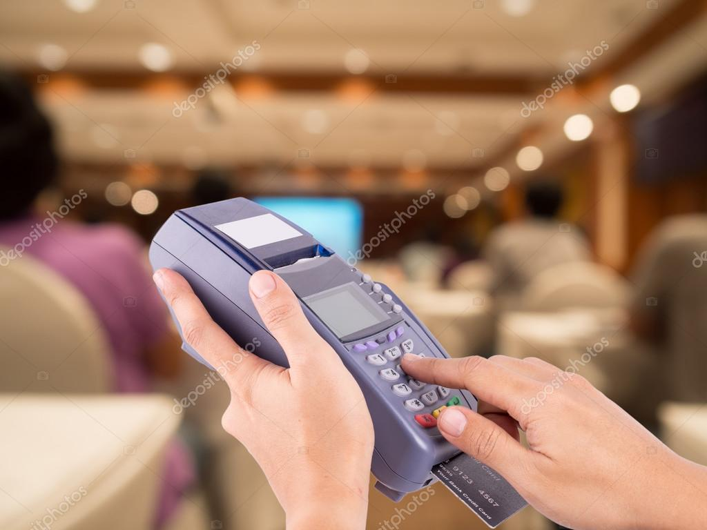Hand Swiping Credit Card Machine with blurred people sitting rea ...