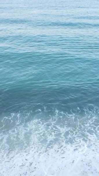 Vertikální video moře u pobřeží - detailní záběr na pobřežní pláň. Zpomalený pohyb