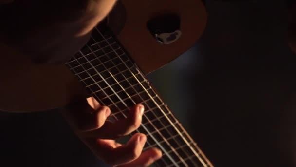 Muž kytarista hraje na kytaru ve tmě. Svislé video