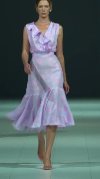 Woman model on the catwalk during a fashion show Vertical video