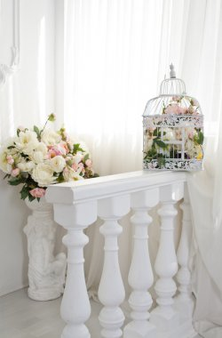 Interior decor with flowers and a white cage