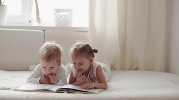 rodina, nevinnost, kojenecké pojmy - Dvě usměvavé děti čtou na posteli velkou zajímavou knížku pohádek. Sourozenci malý chlapec a dívka bratr a sestra bavte se, šťastné děti v karanténě doma