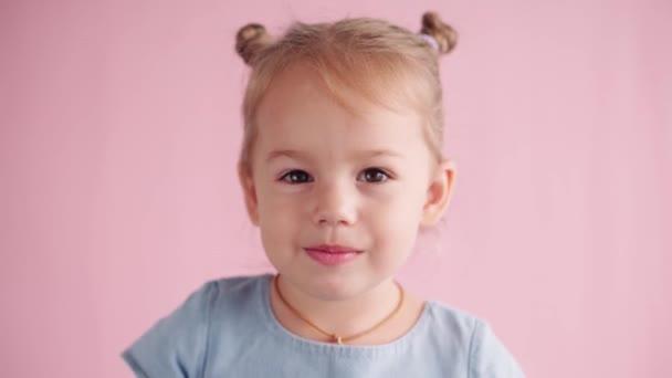 dětství, oslavy, narozeniny, herní koncept - close-up šťastný malý blond-vlasy dívka v modrých šatech při pohledu na kamery kryje uši křik a ukazuje různé emoce na růžovém pevném pozadí.