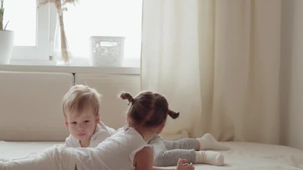 family, innocence, infant concepts - Two smiling children fight, fool around, tease on bed. Siblings little boy and girl brother and sister have fun and laughing, happy kids on quarantine at home.