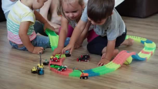 Childhood, games, upbringing and development concept - general plan of mom with children boy brother and girl sister baby play with magic road in kid playroom. Siblings have fun at home on quarantine