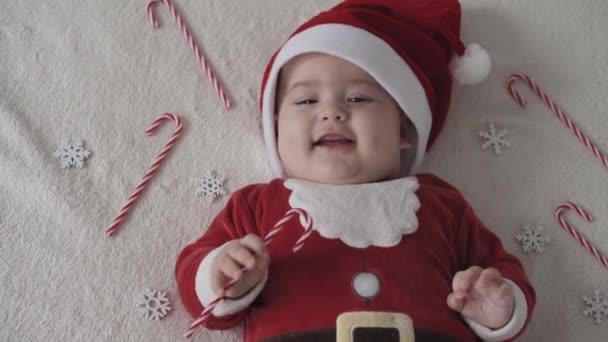 veselé Vánoce a šťastný nový rok, kojenci, dětství, dovolená koncept - close-up 6 měsíců staré buclaté baculaté dítě v Santa klobouku a červené bodysuit ležící na zádech a hrát si s vánoční cukroví usmívající
