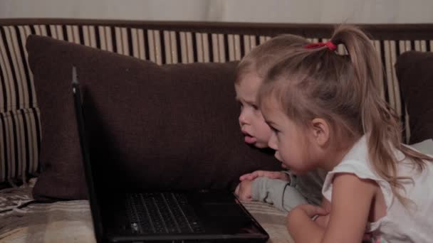 family, game, quarantine, childhood concepts - close up Two happy young children watching cartoons on laptop lying on brown sofa at home during quarantine. Kids siblings brother, sister have fun