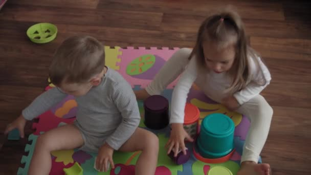 Childhood, family, insulation concept - group two small children collect soft puzzles fruits of big parts sitting on floor. kids Brother and sister playing educational games for motor skills at home