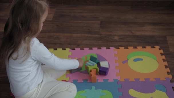 Childhood, family, insulation concept - One cute small happy child build wooden pyramid sitting on floor colored soft mat puzzle. kid girl playing alone educational games for motor skills at home.