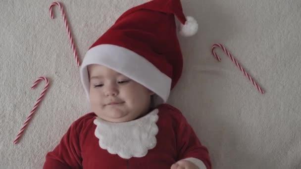 Frohe Weihnachten, frohes neues Jahr, Säuglinge, Kindheit, Urlaubskonzept - Nahaufnahme lächelnd 7 Monate lustiges Neugeborenes in Weihnachtsmann-Mütze, roter Body-Anzug-Spiel auf weißem weichen Bett spielen süße Weihnachtsbonbons lecken
