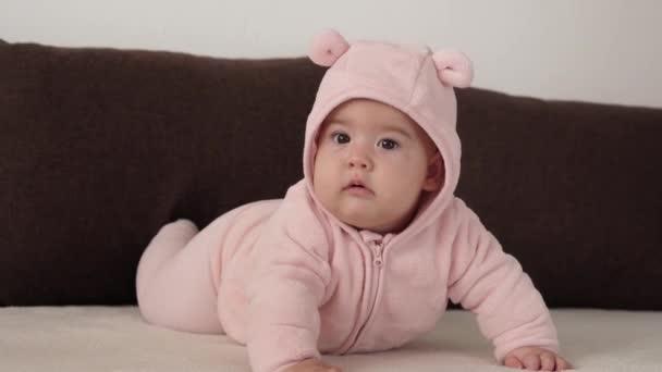 csecsemő, gyermekkori koncepció - közelkép mosolygós boldog kövér vicces barna szemű pufók arca újszülött gyerek ébren. fogatlan 7 hónap baba grimasz, becsukja a szemét feküdt puha ágy rózsaszín flips át has.