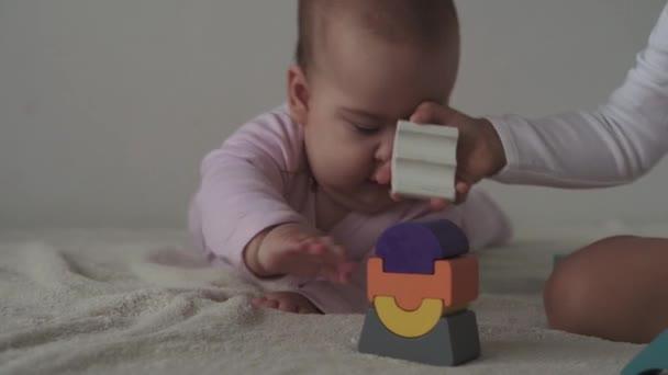 Gyermekkor, család, szigetelés, építési koncepció - 2 kis boldog gyermek épít fa piramis ül az ágyon. újszülött lány 6-9 hónap és a fiú 2-3 éves játszik a motoros készségek otthon.