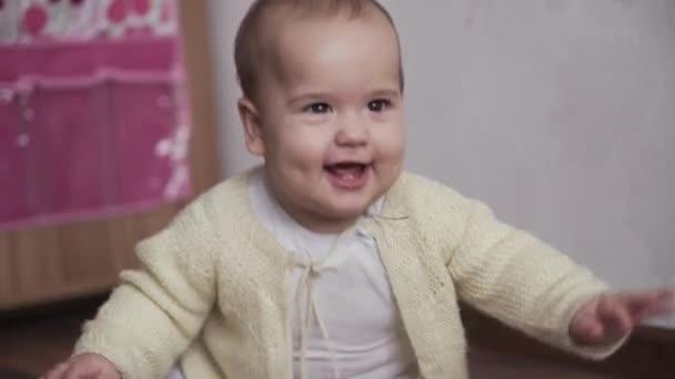 kojenecká, dětská koncepce - veselá veselá hravá batolata dítě 8 měsíců holčička se učí sedět samostatně hrát v herně. úsměv baculatý aktivní vzhůru novorozenec v bílém plazit se po kolenou podlahy doma