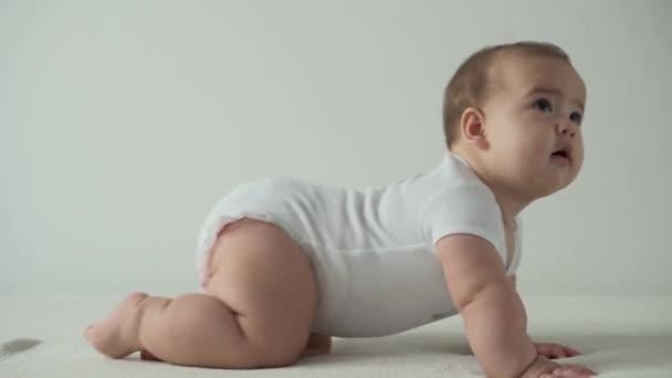 kojenecká, dětská koncepce - šťastná veselá hravá batolata dítě 8 měsíců holčička se učí sedět samostatně hrát na posteli. úsměv baculatý aktivní probuzení novorozenec plazit na kolenou doma na bílém pozadí