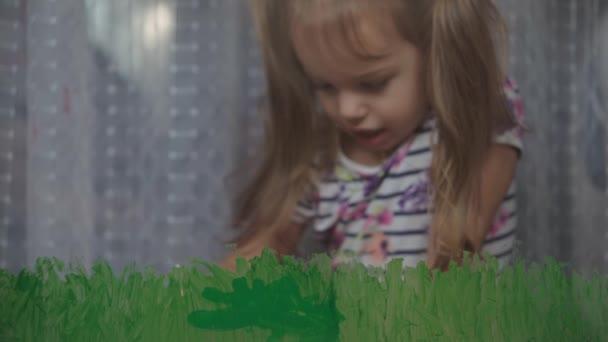 Gyermekkor, kreativitás, természet, tavasz, nyári koncepció - közelkép aranyos kislány 3-4 éves felhívni akril színek ablak üveg. óvodai gyermek festék táj: nap, fa, felhő, eső, virág