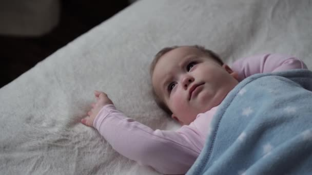 infancy, Relaxation, Sweet Dreams, Childhood, Family Concept - Chubby Little 9-12 months Old Baby child rub her eyes on white Bed Covered by blue Blanket. kid girl wakes up stretches. Lunchtime Mode.