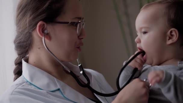 Medizin und Gesundheit, Kinderheilkunde, Covid-19-Konzept - junge Krankenschwester oder Kinderärztin kaukasisch-slawischen Aussehens in Nahaufnahme halten Säugling von 8-12 Monaten in den Armen vor Fensterhintergrund