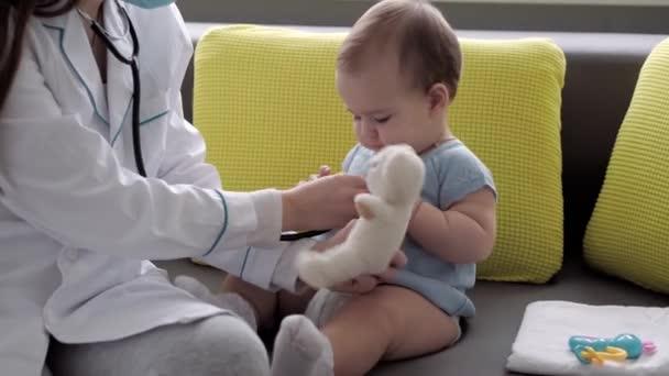 Medizin und Gesundheit, Kinderheilkunde, Covid-19-Konzept - junge Krankenschwester oder Kinderärztin kaukasisch-slawischer Herkunft untersucht Säugling von 8-12 Monaten auf gelbem grauen Sofa gegenüber dem Fenster