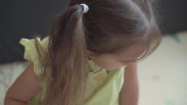 autentický roztomilý šťastný dítě školka dívka klade puzzle horní pohled zblízka. malý kluk hrát sám vzdělávací hry pro motorické dovednosti v blízkosti žluté šedé pohovky. Dětství, rodina, koncepce izolace.