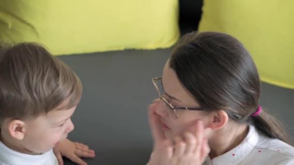 Autentická mladá běloška se stará o děti. Máma si to doma užívá s dětmi. Malý školáček a holčička s matkou se baví trávit čas uvnitř. Mateřství, koncept dětství.