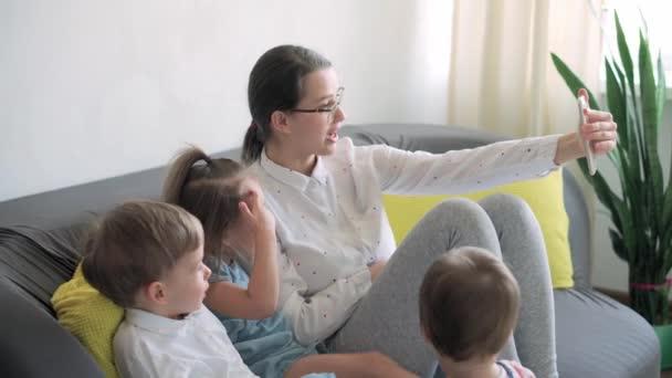 kaukázusi család kisgyermekek fiú és anya beszél videokonferencián okostelefonnal együtt nappaliban otthon boldog mosollyal. tevékenység technológia életmód mobiltelefon-használat koncepció