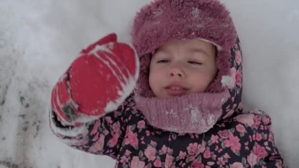 Urlaub, Spiel, Kindheitskonzept - slo-mo authentisch glücklich Vorschulkind Baby Girl Lächeln liegt im Schnee auf dem Rücken und applaudieren mit Füßen machen Engel. Schneefall in der kalten Jahreszeit im Winter im Freien