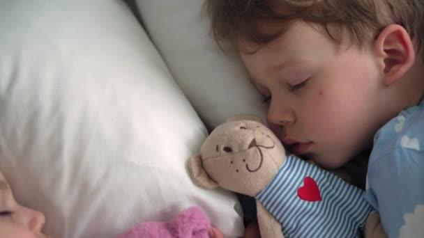 top view autentikus aranyos kaukázusi kis óvodás testvérek baba fiú és lány kék rózsaszín pizsamában aludni teddy maci fehér ágyon. gyermek pihenés, gondozás, orvostudomány és egészség, gyermekkor, életkoncepció