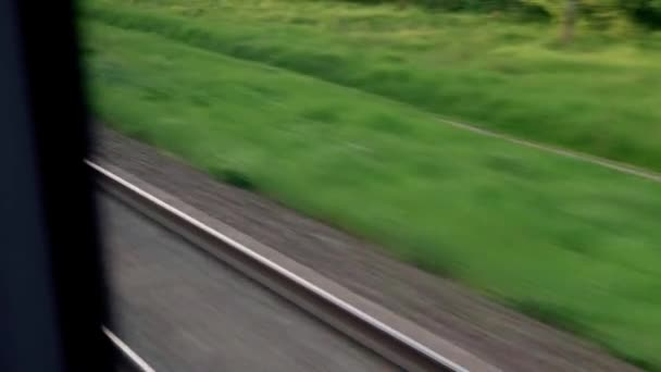 pohled z okna rychlovlaku se záři na sklo a paralelní kolejnice na krajinu luk a lesů před západem slunce v letním pozadí. Doprava, cestování, silnice, železnice, koncept smilstva