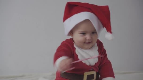 Veselé Vánoce, šťastný nový rok, kojence, dětství, dovolená koncept - close-up úsměv 7 měsíců legrační novorozenec v Santa Claus klobouk, červená bodysuit hrát sedí na teplé měkké posteli lízat sladké vánoční cukroví