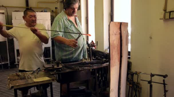 Glassblower works with assistant on a handcrafted piece