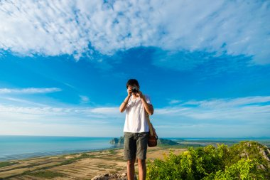 Artist men standing on top of mountain cliff and enjoying take p