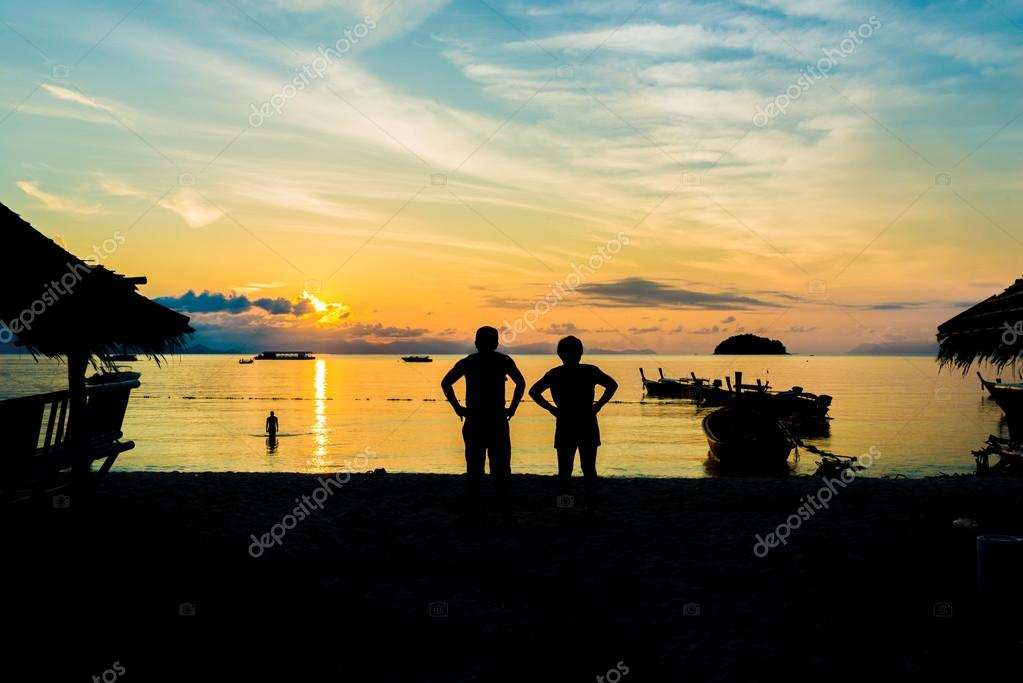 Silhouettes of young couple of people on beach