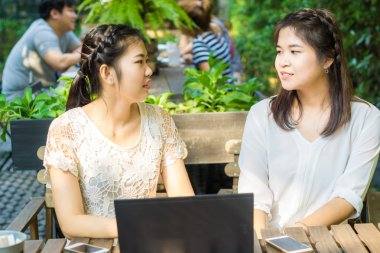 Two asian young female friends use internet together on laptop outdoor