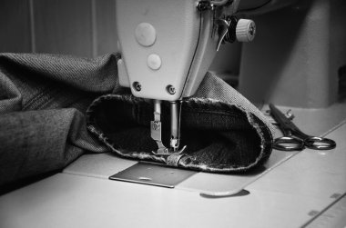 Sewing machine and jeans in sewing workshop. monochrome