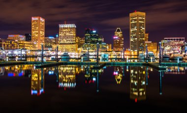 The skyline and docks reflecting in the water at night, in the I